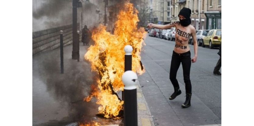 Trois féministes du mouvement des Femen ont brûlé mercredi le drapeau salafiste devant la Grande Mosquée de Paris pour exprimer leur solidarité avec une militante tunisienne et dénoncer les atteintes aux droits des femmes dans les pays arabo-musulmans. (c) Afp