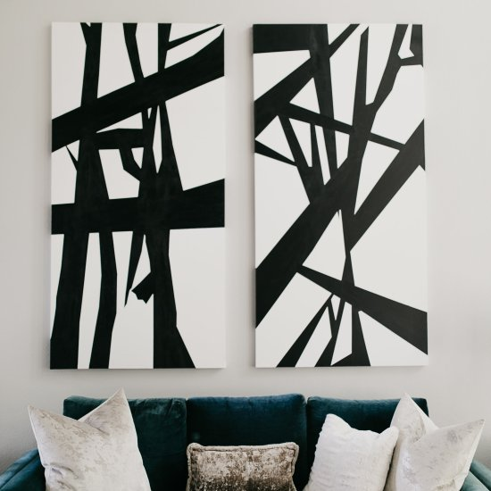 Black and white abstract painting above teal couch