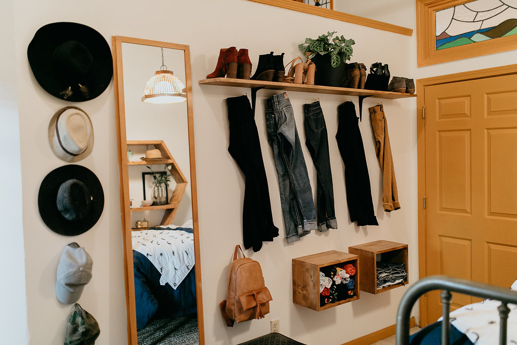 Clothes and hats hung on wall, boutique style shelving