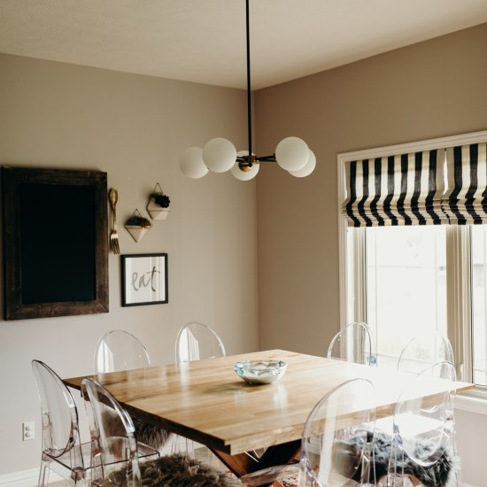 Transparent kitchen chairs and wooden table on orange area rug