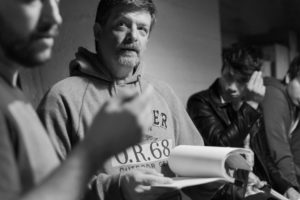 Director Shawn Justice looks over the script as he discusses the upcoming scene with Kevin Hayes, the Director of Photography.