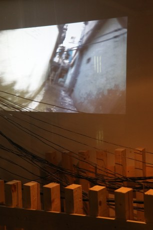 A projection of Burj al-Barajneh camp over the 'wires' hanging over the narrow alleyway 'reconstructed' in the gallery. (c) E. Fiddian-Qasmiyeh