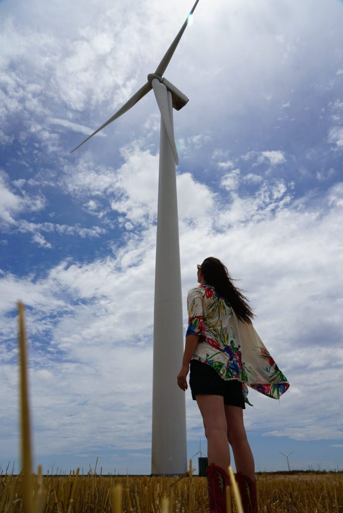Woman Looking at wind turbine, wondering how to use green energy in New York City.