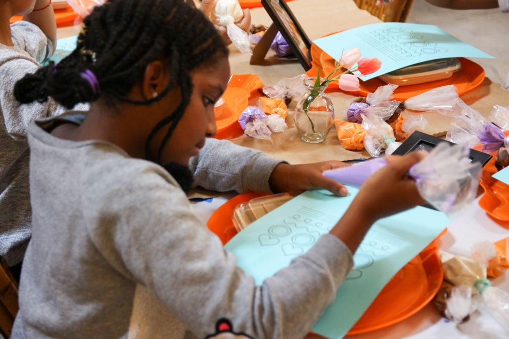 Children practice frosting at educational workshop for youth on custom desserts