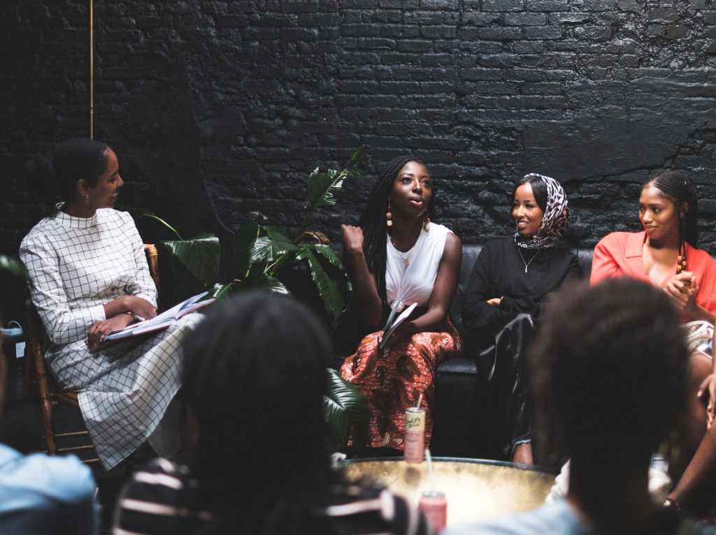 African American women sit talking in an room painted all black at Regency Black Room