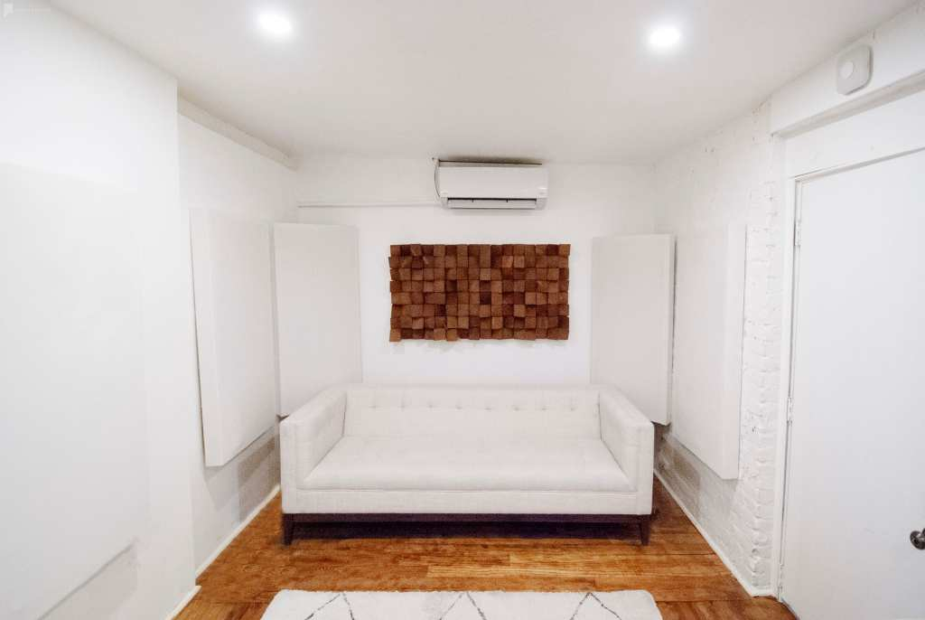 All-White room with acoustic paneling and a white couch at the Regency Recording studio