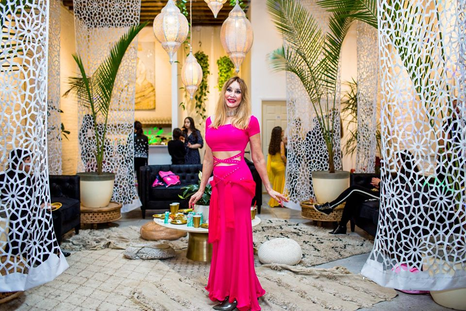 Belly dancer poses in pink garb in Regency Event Venue's White Room