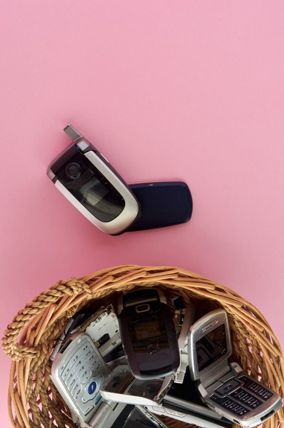 wicker basket, with broken mobile phones, recycling technology, early 2000s on pink background and copy space,.