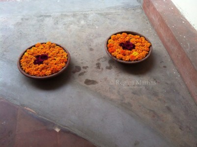 "There are flowers wherever one goes in India. Bowls of bright orange marigolds at the bottom of a stairwell. The Portuguese introduced marigolds to India. They are also known as ""The Herb of the Sun"" and are symbolic of passion and creativity. Curtains of marigolds are strung up at Hindu weddings. Lord Vishnu and his wife Goddess Lakshmi, the ideal couple are worshiped with marigolds, hence they are auspicious at Hindu weddings, blessing the couple divine blessings and a happy and prosperous life ahead."