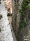 A narrow steep staircase flanked by a great big ancient wall ©2016 Regina Martins