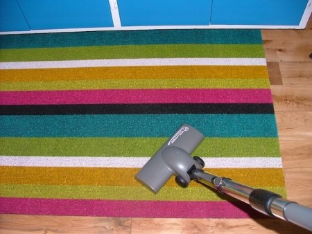Canister vacuum cleaner: Turbo carpet brush used on kitchen floor mat.