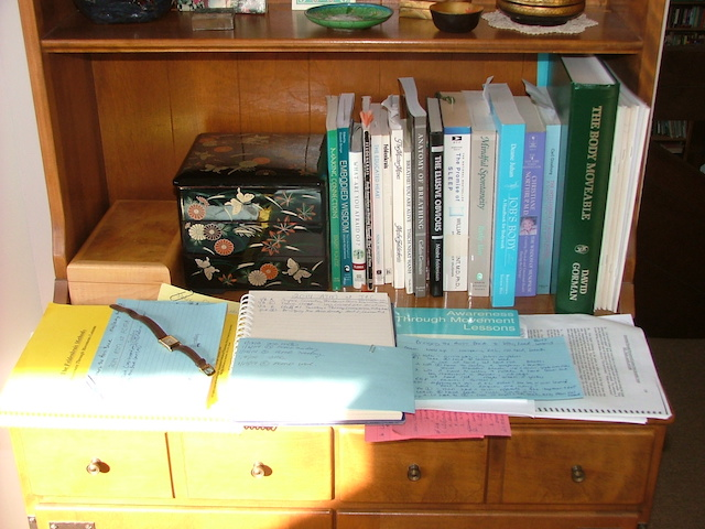 Movement therapy books on wood desk with hand-written note cards. And a wrist watch.