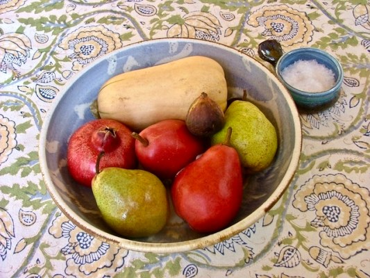 Butternut squash, pears and a fig. All fresh, on tablecloth with bowl of sea salt.
