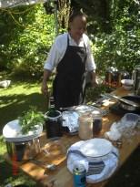 Koch hinter der Anrichte im Garten