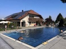 Beheizter offener Swimmingpool BL 7x15 m im Vordergrund. Bistro Grenzenlos mit Camping Reception im Hintergrund