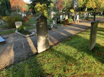 Na de aanleg van een looppad heeft deze grafsteen een beetje vreemde plek gekregen. . Licentie CC-BY. Foto: Regionaal Archief Alkmaar