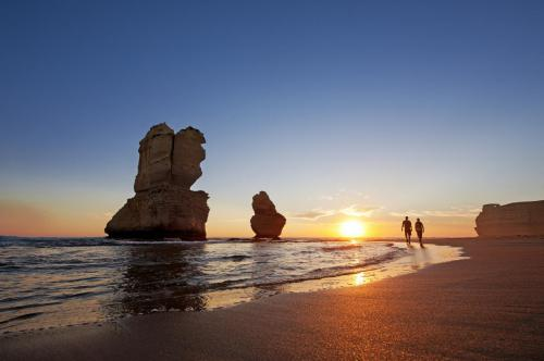 Couple hike past the Twelve Apostles at sunset