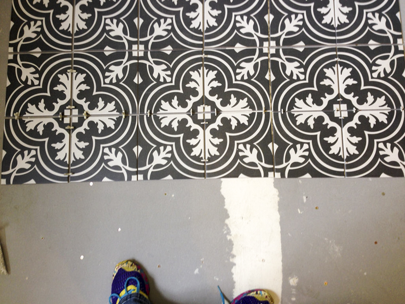 Laying encaustic decorative tile in a bathroom.
