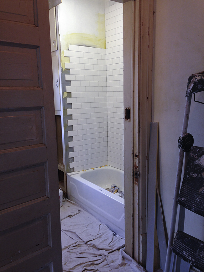 Subway tile being installed in a victorian bathroom.