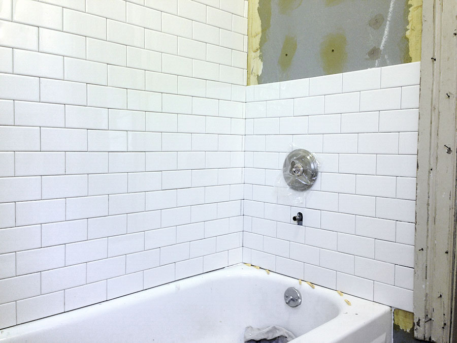 Progress being made tiling a tub surround in a Victorian bathroom.