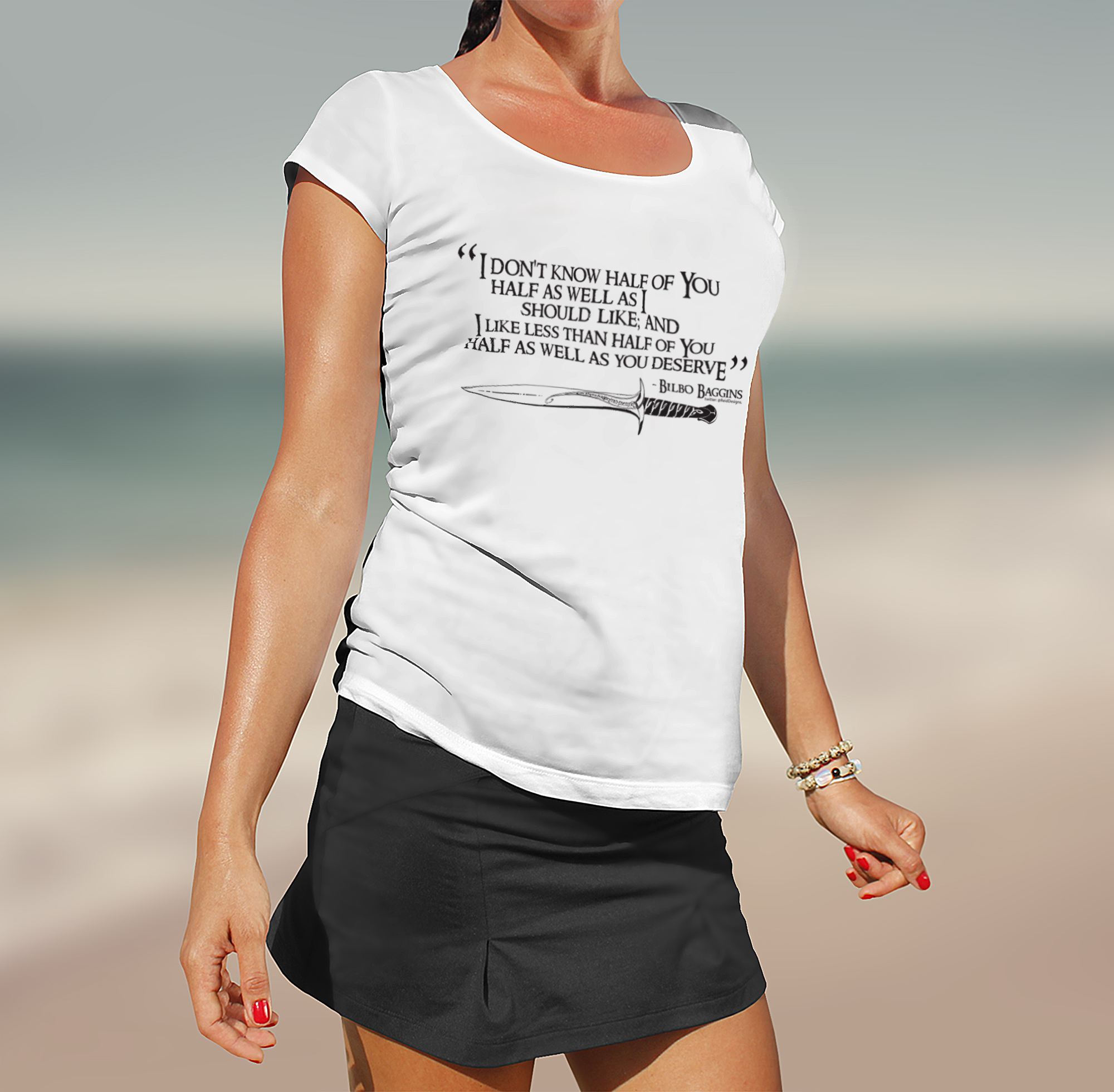 Woman on beach wearing a white tshirt with the quotation from the Lord of the Rings printed on the front.