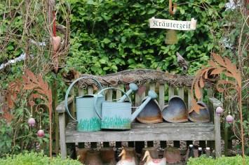 alte Gießkannen und Blumentöpfe auf Holzbank