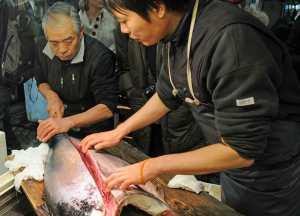Zwei Männer filetieren einen Fisch.