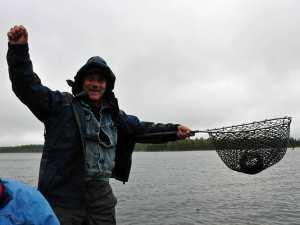 Mann mit Kescher und Fisch