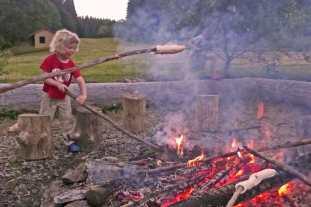 Ein kleiner Junge stochert in einem Feuer, andere Kinder halten Stockbrote über die Glut