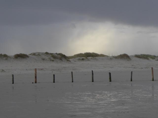 Sonnenstrahlen kämpfen ich durch Wolkenschleier an der Nordsee