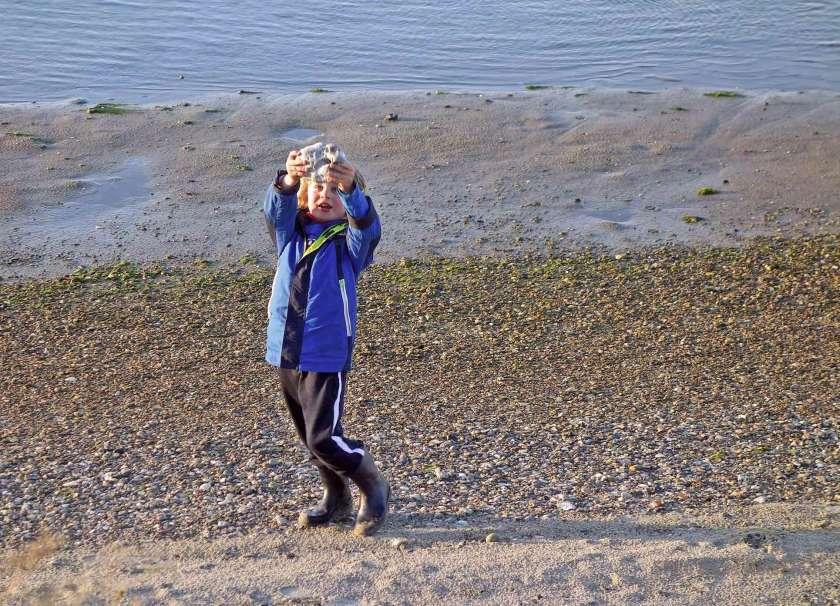 Ein Kind hat am Strand einen Hühnergott gefunden und hält ihn hoch