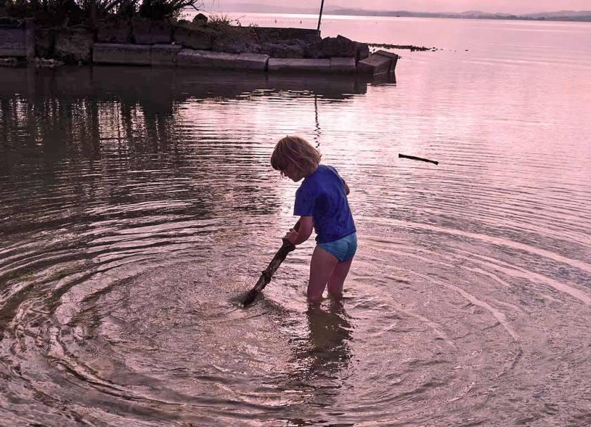 Kind spielt mit einem Stock im Cheimsee