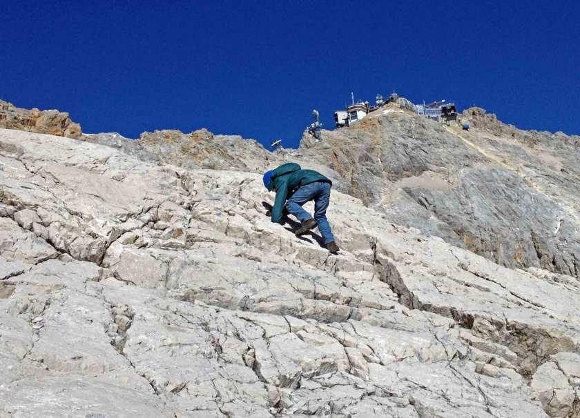 Kind klettert Felswand auf der Zugspitze hoch