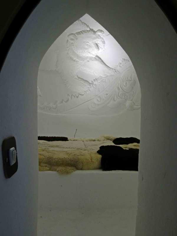 Blick durch die Tür in ein Iglu auf der Zugspitze mit einem Bären-Relief aus Schnee