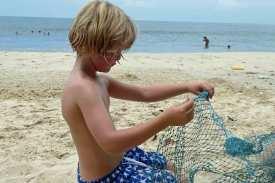 Kind im Glück mit einem echten Fischernetz, das es gefunden hat