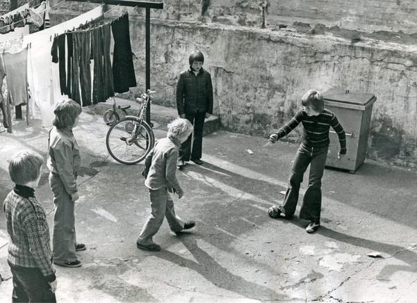 Gutter i slengbukser i bakgård i Oslo