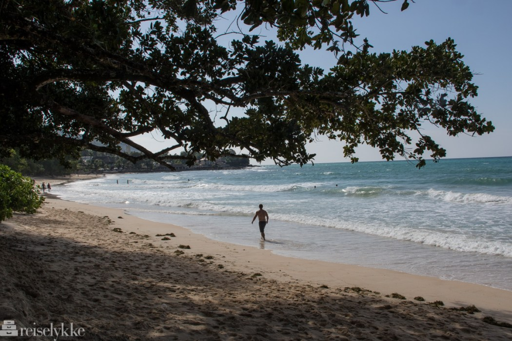 Mann på stranden Beau Vallon, Mahé, Seychellene