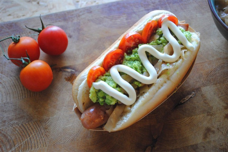 Chili: hot dog in een broodje met gesneden tomaten, zuurkool, geplette avocado en mayonaise. © bimbim101