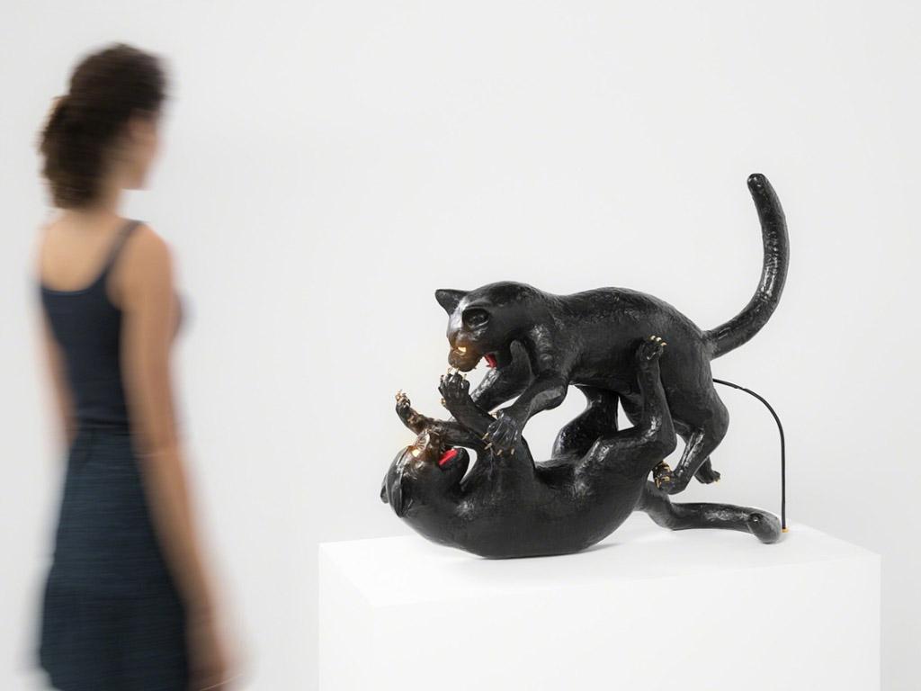 Seletti Cat lamp kat met gouden ballen en lichtgevende ogen kunst op kantoor