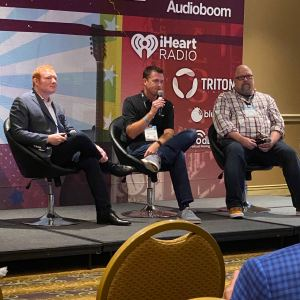 Three men sitting on stage at Podcast Movement 2021