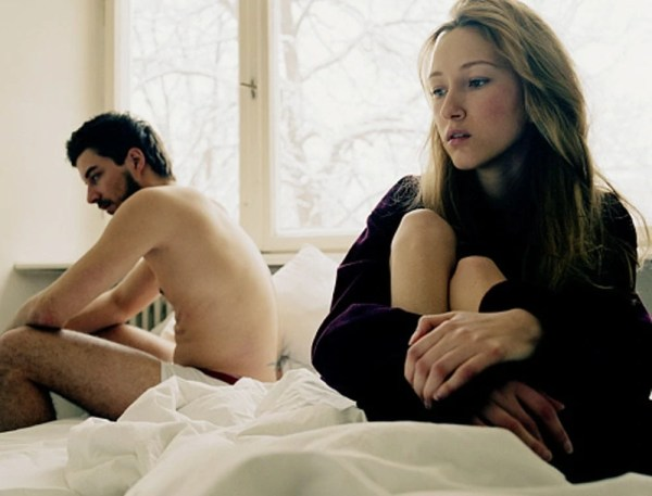 Young woman sitting in bed, man sitting on edge of bed in background