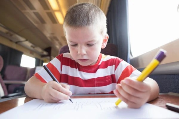 Young boy with pencil, pen and paper on train, with no adults in sight.