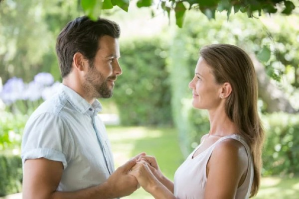 Couple holding hands face to face in garden