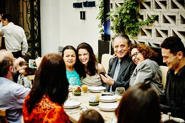 Laughing family taking photos during dinner party