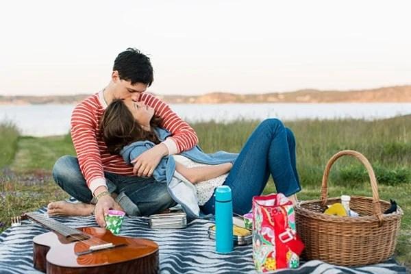 Man kissing girlfriend during picnic