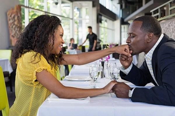 African American man kissing girlfriend's hand in restaurant