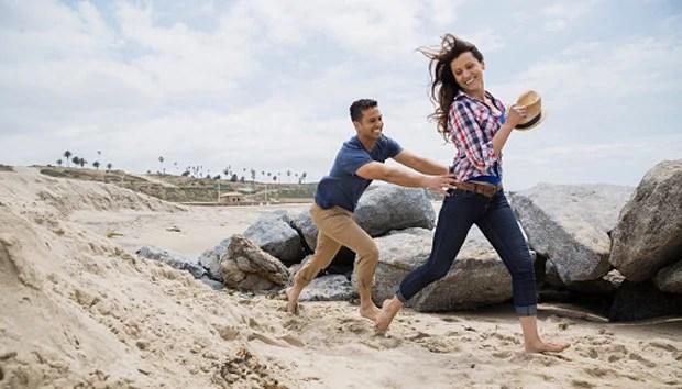 Playful couple running on beach