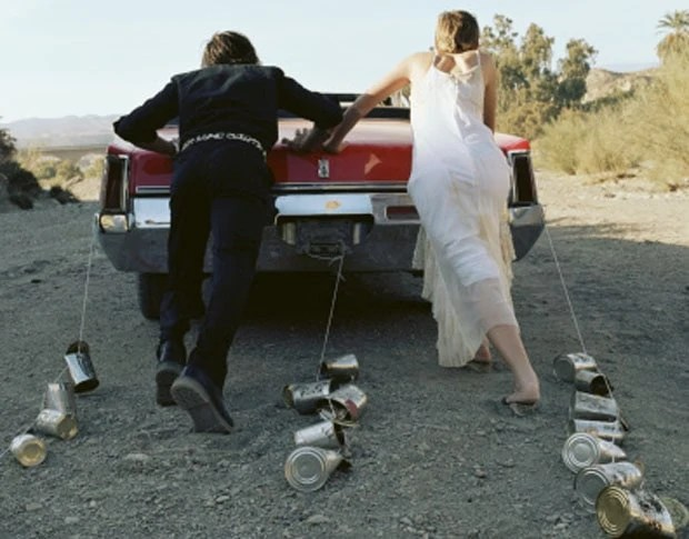 Bride and groom pushing car