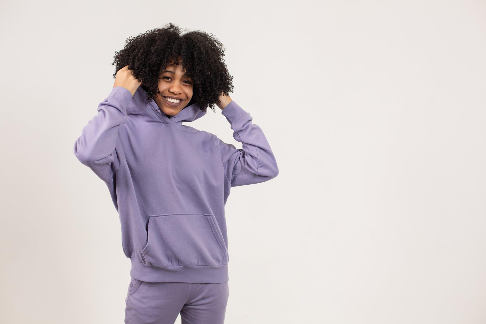happy black lady wearing hoodie in studio