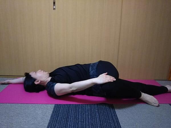 対角線に手足を延ばし、曲げた左足を右手で押さえる写真